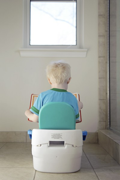 Toddler blonde boy sitting on a potty reading a book