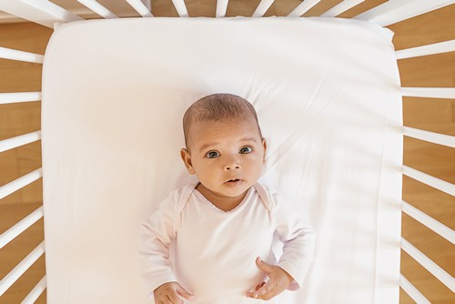 Cute Baby Girl Lying in the Crib