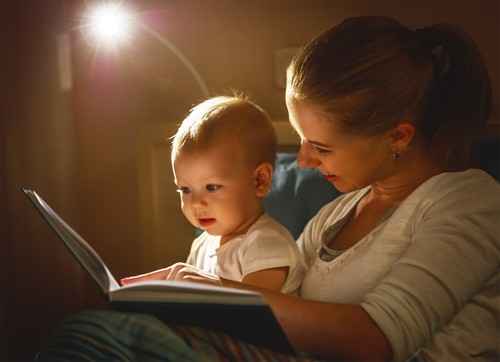 mother and baby son reading a book in bed before going to sleep